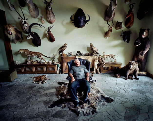 "Rafal Milach, ""Local collector and hunter posing for portrait in his trophy hall"""